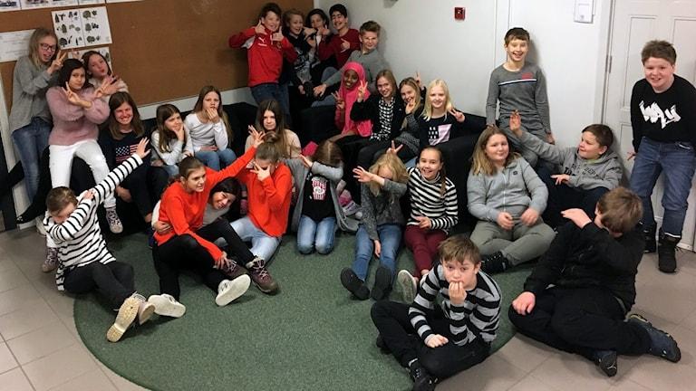 Klass 5C Engelska skolan sitter på tillsammans på golvet och busar. Foto: Mikael Häggqvist