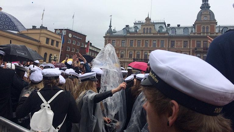 Mösspåtagning i strilande regn för studenterna på Stora torget. Foto: Ingrid Engstedt Edfast/Sveriges Radio