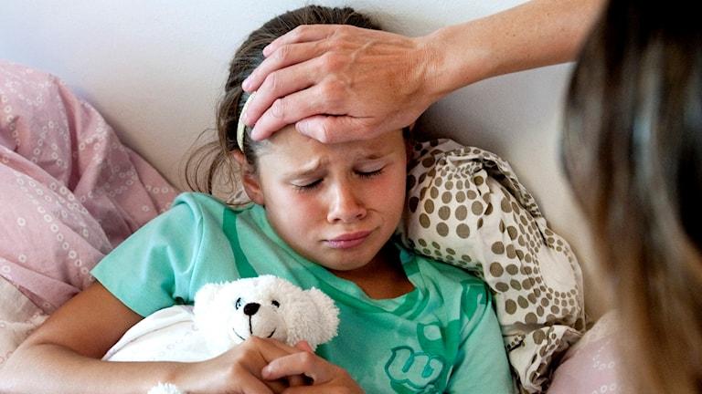 Sängliggande liten flicka med feber pysslas om av vuxen. Hon kramar en gosenalle.
