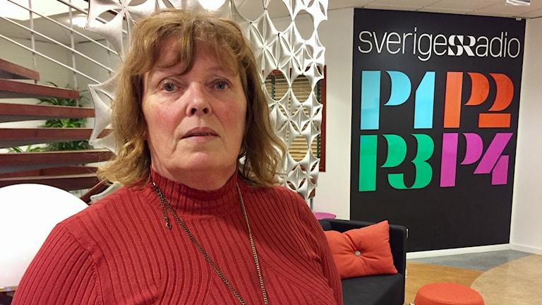 Carina Ytterström står i P4 Västernorrlands foajé i en röd tröja och med ett långt halsband. I bakgrunden syns en fondvägg där Sveriges Radio står i Stora bokstäver. Foto: Alexander Arvidsson/Sveriges Radio