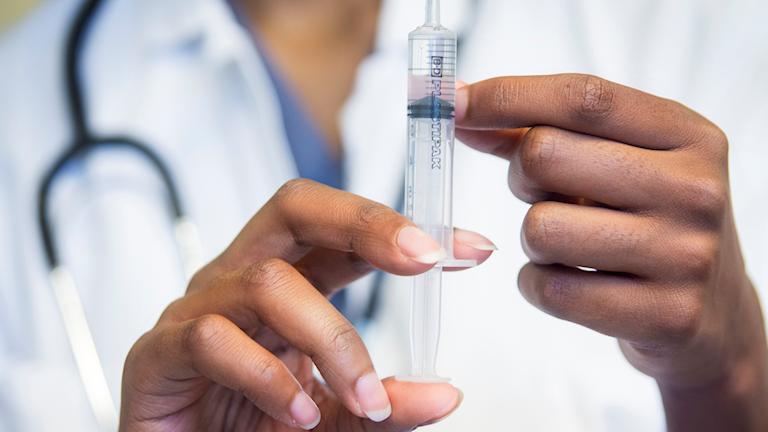 Kvinnlig läkare preparerar spruta