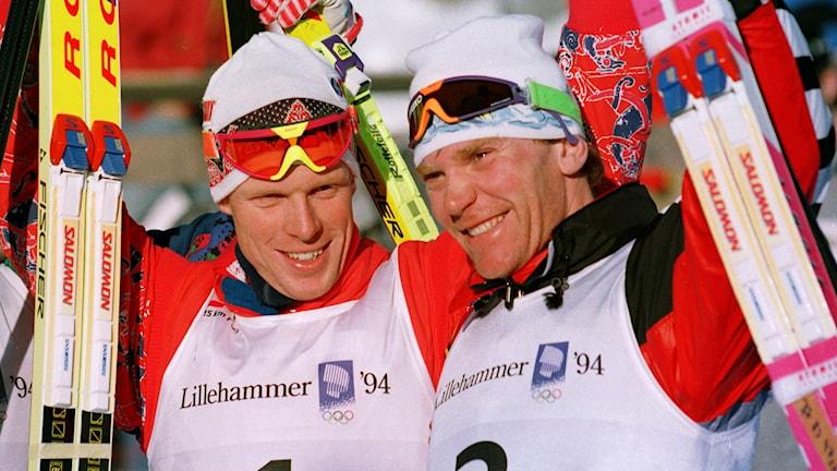 Björn Dählie och Vladimir Smirnov står tillsammans och sträcker skidorna mot himlen efter guld och silver i 15 km jaktstart i OS i Lillehammer 1994. Foto: Björn Sigurdsön/TT