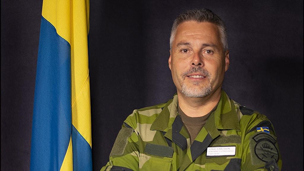 Man i camouflagekläder står vid blågul flagga