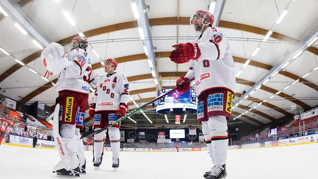 Tre ishockeyspelare i vita dresser står på ishockeyrinken.