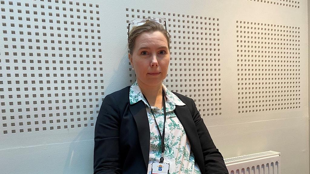 En bild på åklagare Karin Everitt som sitter med en gul pärm i knät.