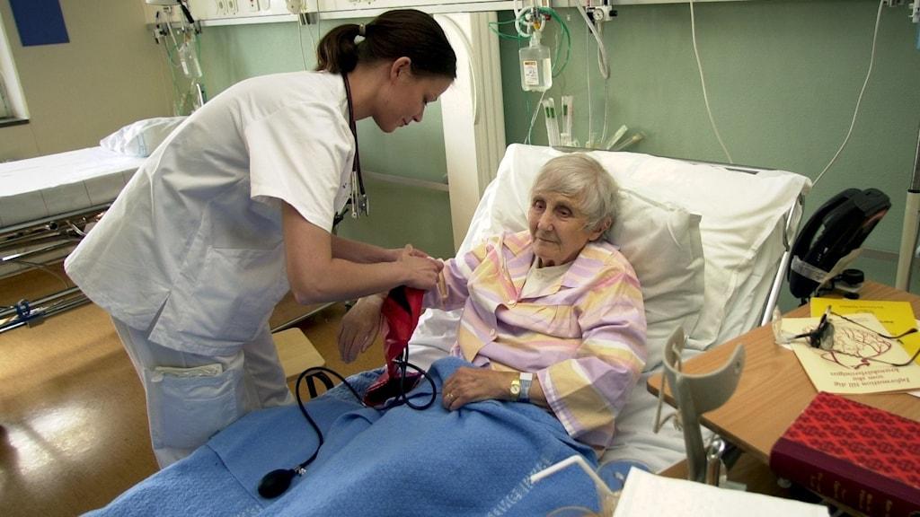 Sjuksköterska kontrollerar blodtrycket på äldre sängliggande kvinna. Foto: Fredrik Sandberg/SCANPIX
