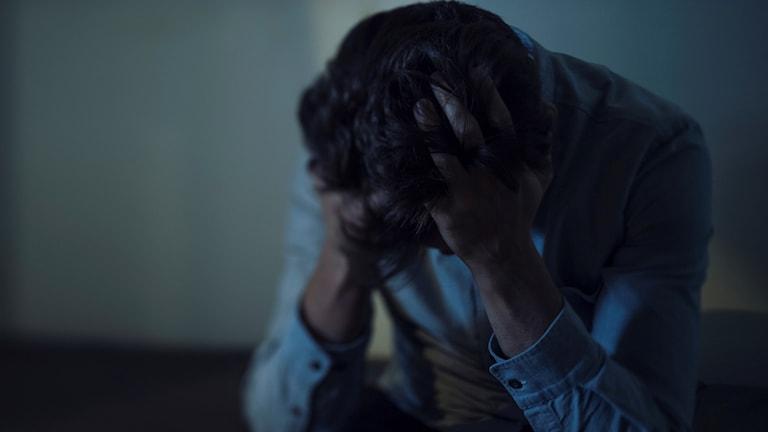 Ung man lutar sitt huvud i händerna och tittar ner. Foto: Stina Stjernkvist/TT