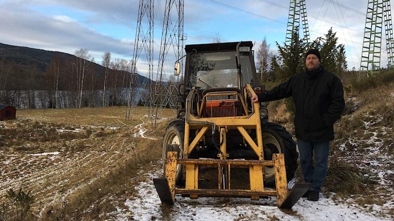 Patrick Glamsjö står vid sidan av sin traktor, en liten fiat med gult frontlastaraggregat som blockerar vägen för grävmaskinerna i Baggböle. Foto: Ingrid Engstedt Edfast/Sveriges Radio