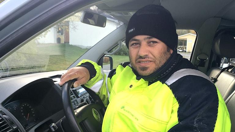 Moustafa Sido sitter på förarplatsen i en bil med ena handen på ratten. Han vänder sig åt vänder mot kameran, har ett tillbakahållet leende och ser in i kameran.