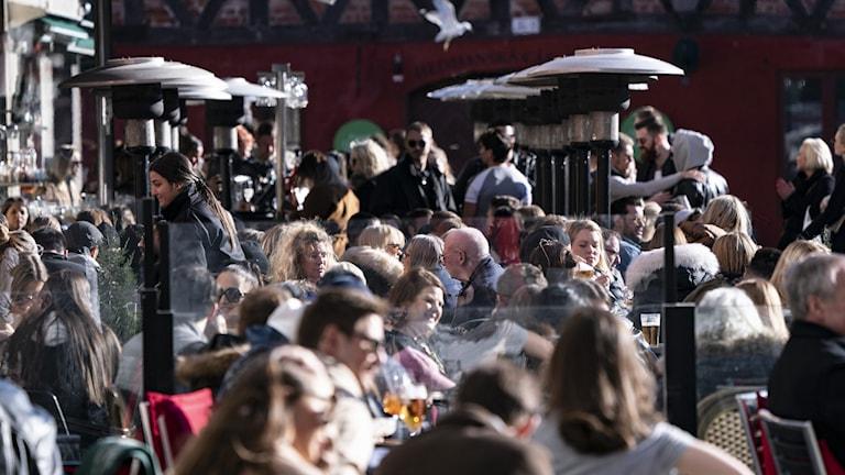 Översiktsbild på en uteservering med massor av människor sitter nära varandra.