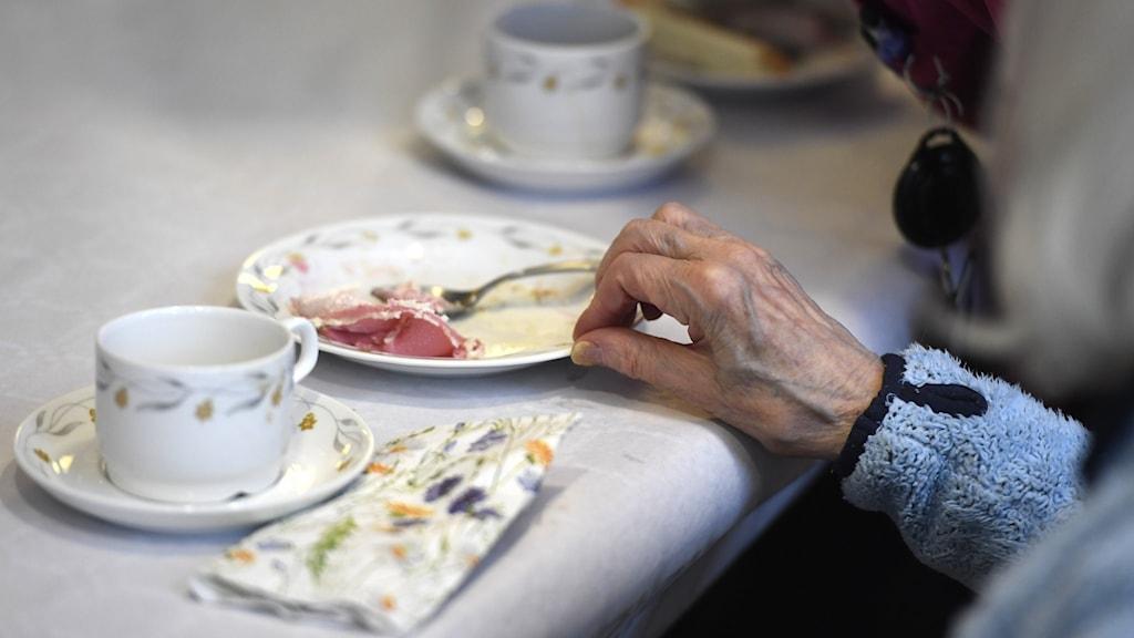 En äldre kvinna dricker kaffe och äter tårta på ett  äldreboende.  Foto: Pontus Lundahl/TT