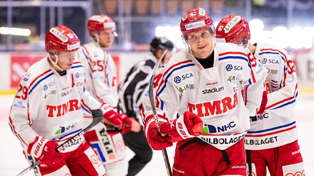 Hockeyspelare med ett leende på läpparna åker i lugn takt mot avbytarbåset.