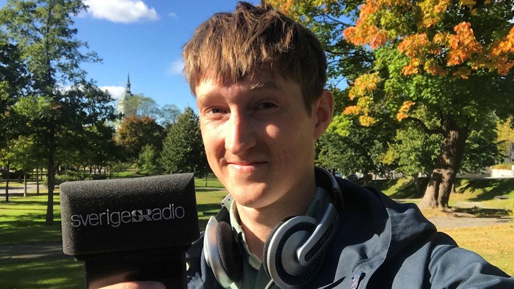 Reporter Joakim Silverdal på Kulturnytt håller upp sin Sveriges Radio-märkta mikrofon. I bakgrunden skymtar Domkyrkan. Foto: Joakim Silverdal/Sveriges Radio