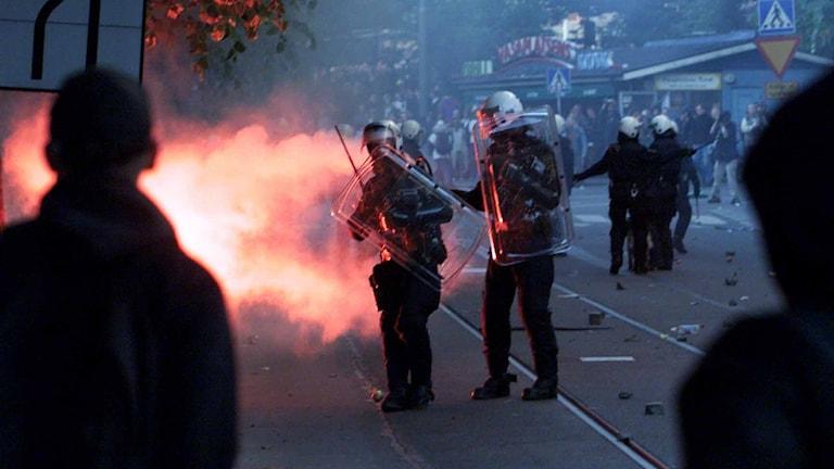 Två poliser i kravallmunderingen kommer gående genom röken från en röd rökgranat vid vasaplatsen i Göteborg. Bilden är från Göteborgskravallerna 2001. Foto: Henrik Montgomery/TT