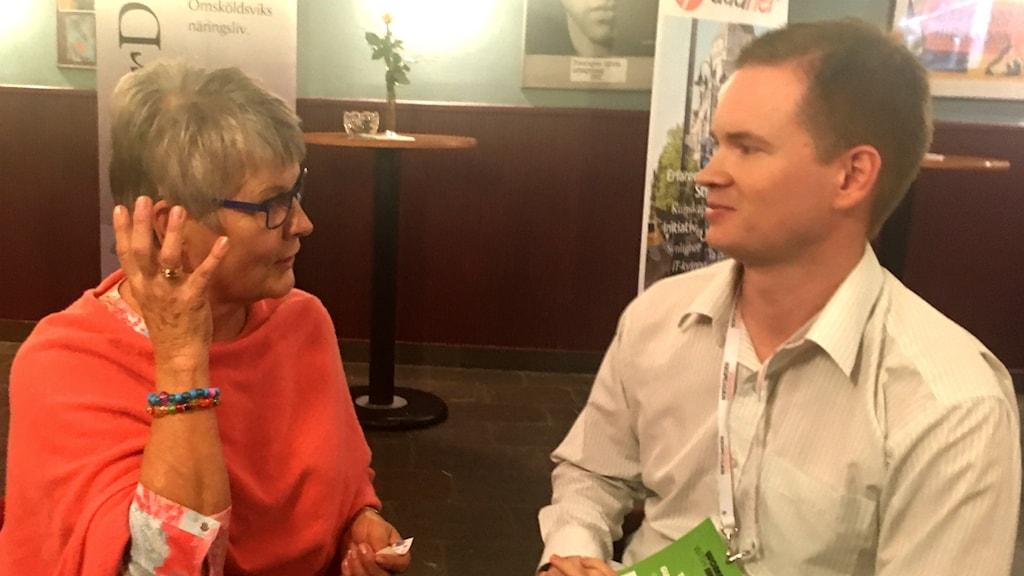 Maud Olofsson i rödrösa poncho pratar och gestikulerar. Tomas Gunnarsson, i vit skjorta, lyssnar.