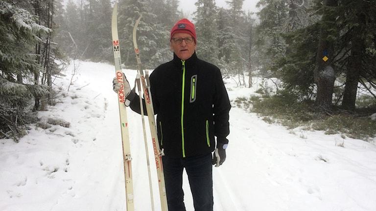 Staffan Olsson står vid skidspåret i Solberg med längdskidor och stavar mot axeln. Foto: Lennart Sundwall/Sveriges Radio