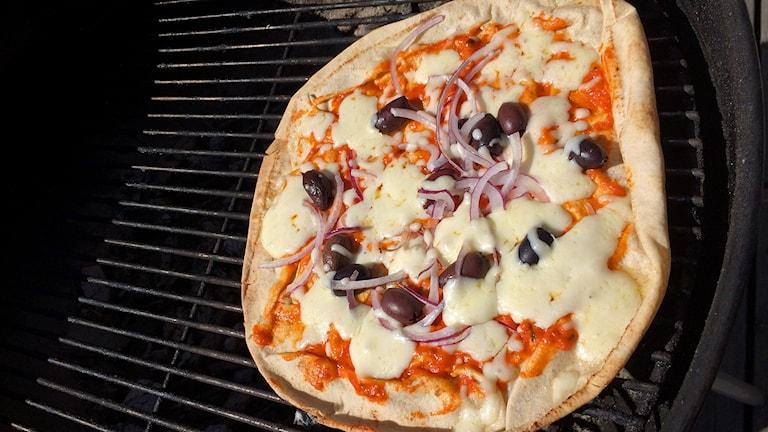Pizza med röd pesto, oliver, ost och rödlök tillagad i en klotgrill. Foto: Ann-Charlotte Carlsson/Sveriges Radio