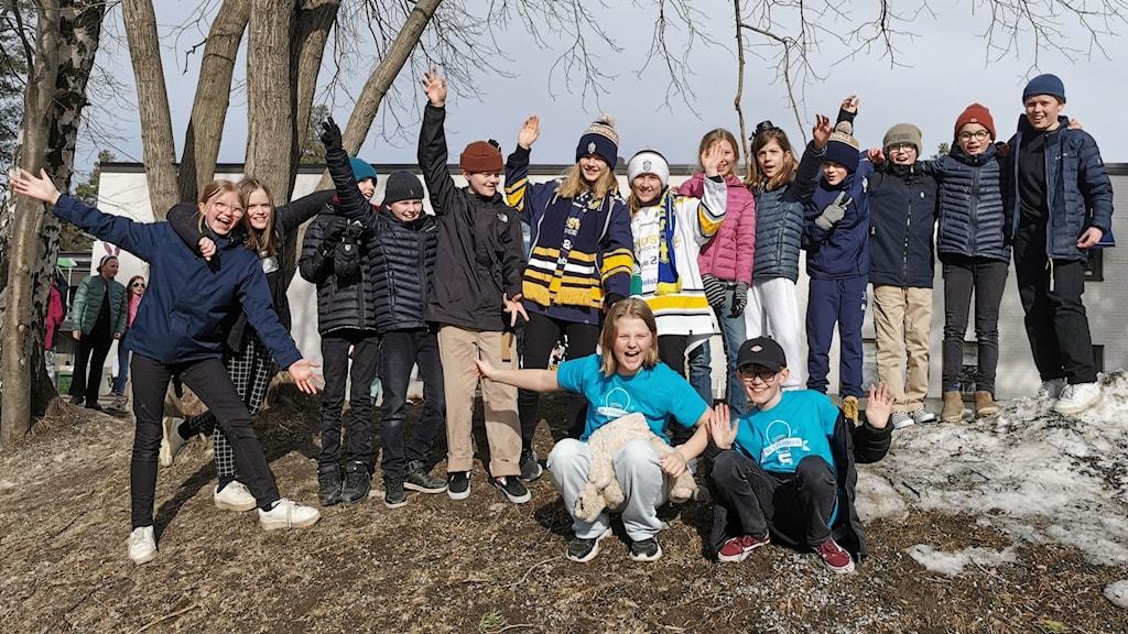 Alla i klass 5:1 på Mimerskolan står på skolgården och är pepp inför tävlingen. Tyra och Alfons sitter hukade längst fram i sina blå tävlingströjor.
