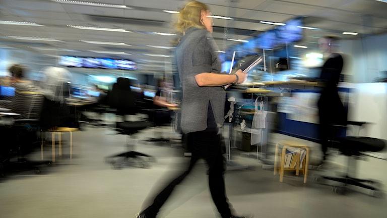 En kvinna går genom ett kontorslandskap och pratar i sin telefon