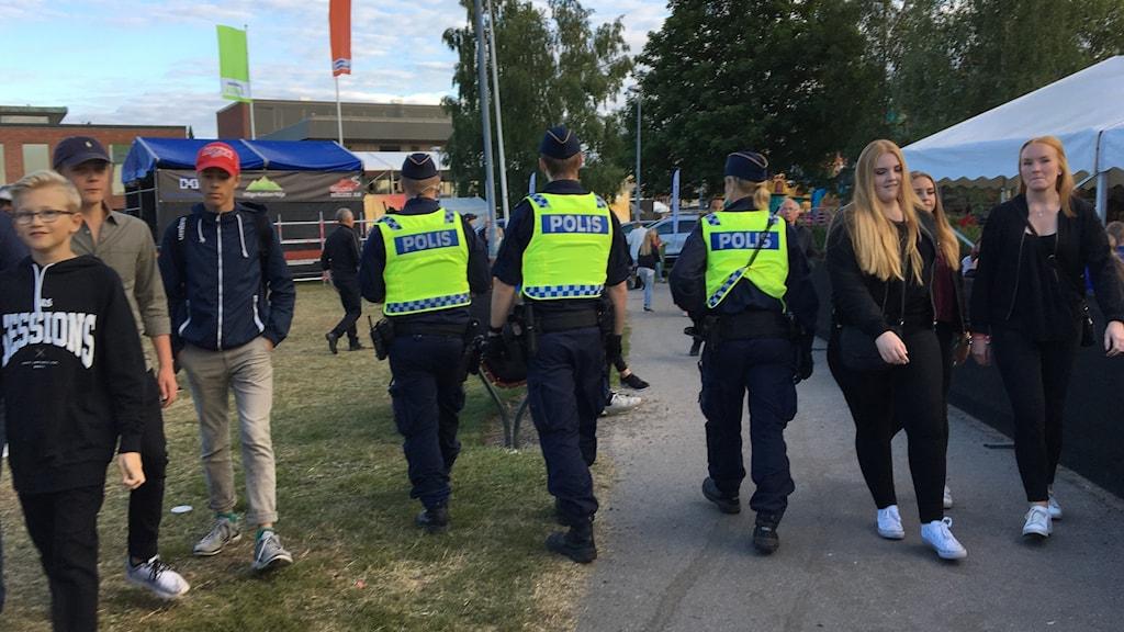 Tre poliser med reflexvästar går igenom en folkmassa under stadsfesten i Härnösand. Foto: Ulla Öhman/Sveriges Radio