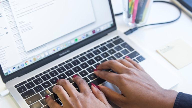 Kvinnas händer som skriver på en laptop