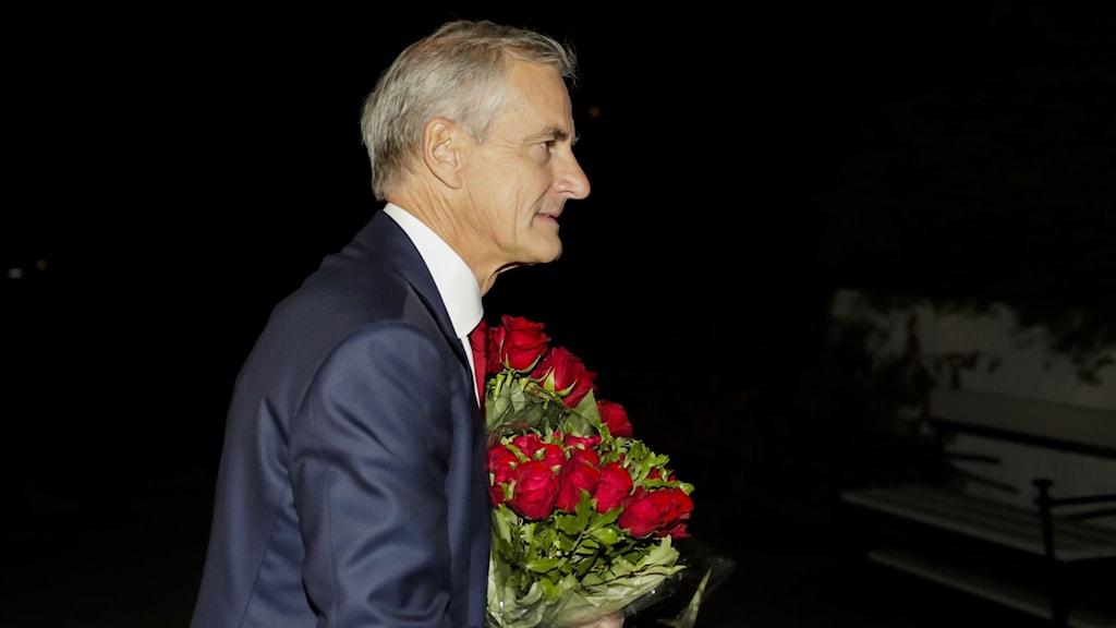 En man i kavaj bärandes på en bukett blommor.