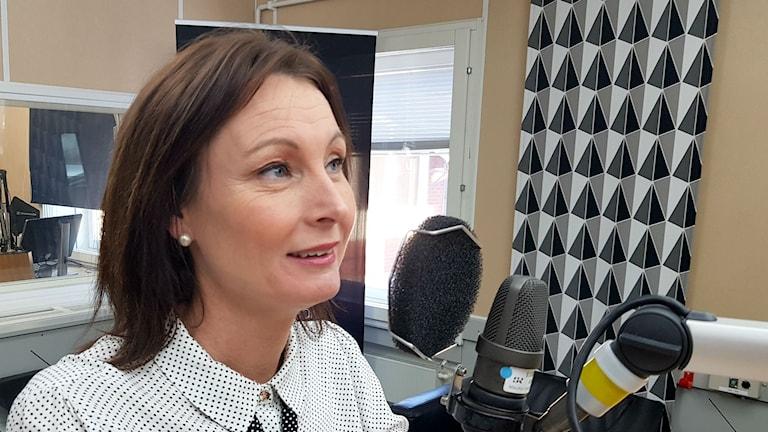 Therese Sjögren med brunt hår och småprickig skjorta tar i en mikrofon.