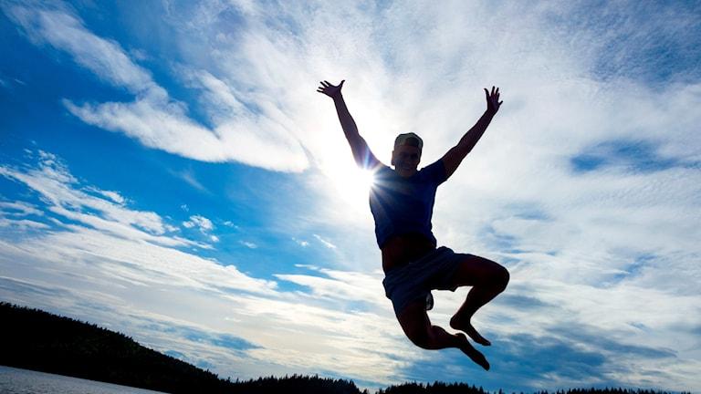 En man hoppar ett högt glädjeskutt i motljus.