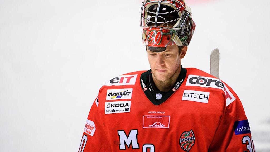 En hockeymålvakt klädd i röd tröja åker över isen med hjälmen uppdragen på hjässan.