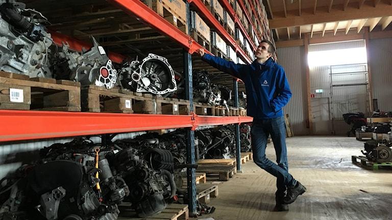 Ådalens bildemonterings VD Johan Axel Forsman lutar sig mot en hylla med reservdelar i en lagerlokal.