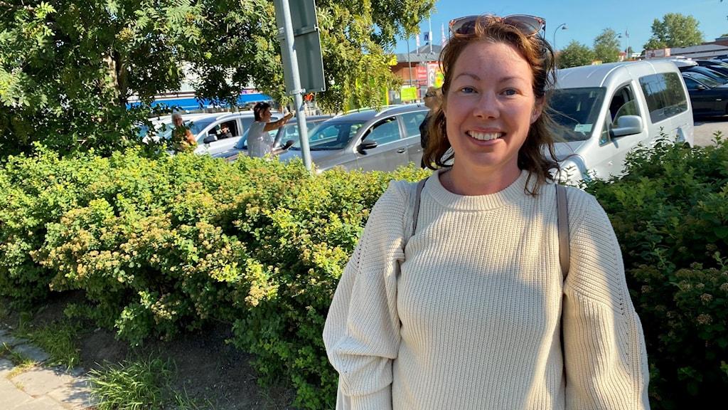 Kvinna med beige tröja vid parkering