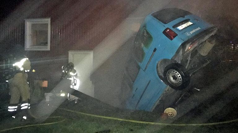 En blå bil från postnord som står med fronten ner i en källaringång vid en husvägg.