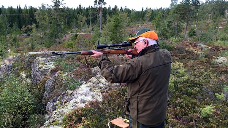 Jaktledare söker av området med kikarsiktet på geväret. Foto: Lotte Nord