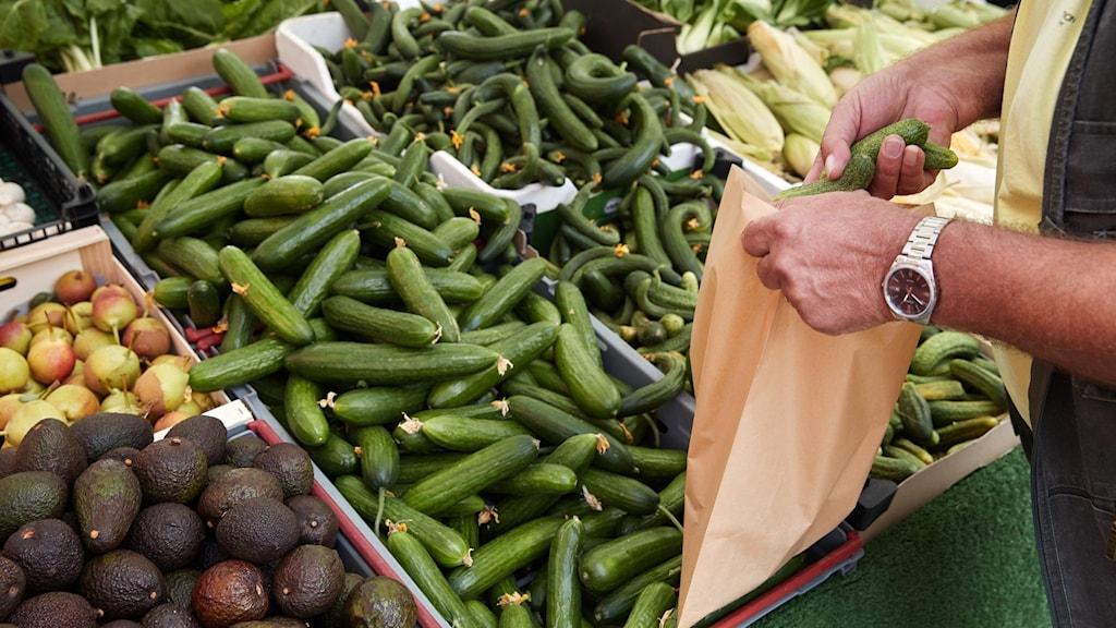 En person fyller en påse med grönsaker från ett stånd.