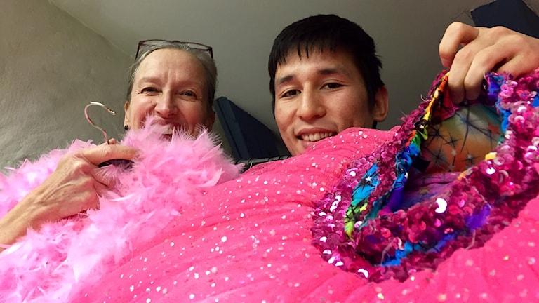 Ann Jerbo och Sharif Moradi tittar upp bakom en rosa tyllkjol. Foto: Karin Lönnå/Sveriges Radio