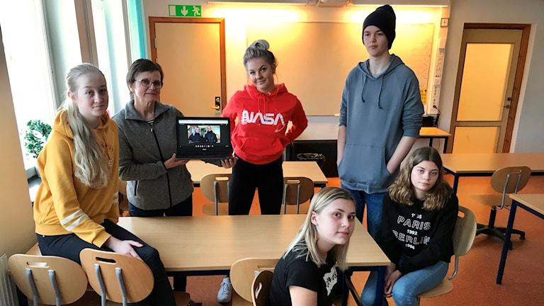 Elever och en lärare i Ramsele skola som håler en dator där deras film visas
