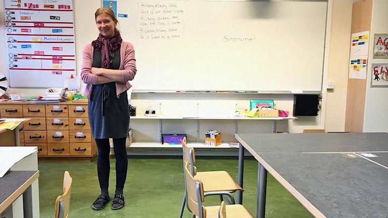 Kvinna i ett klassrum.