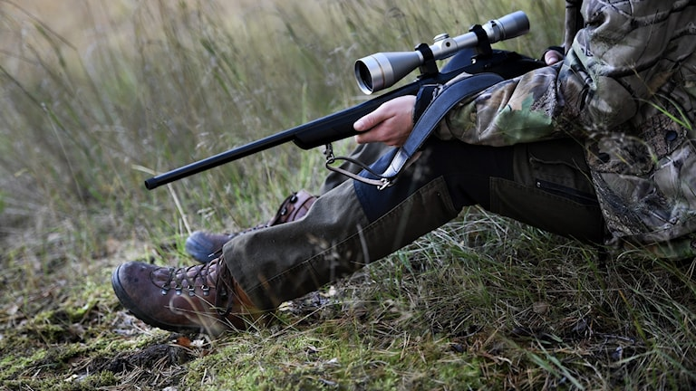 Jägare sitter ner med gevär i handen.