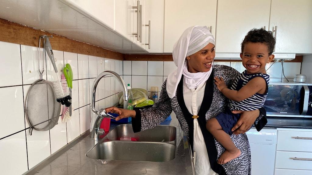 Badria står framför vattenkranen i sitt kök med handen på vredet. På höften har hon ett barn som ler stort och titta nyfiket mot kameran. Badria Ler också med blicken vänd mot barnet.