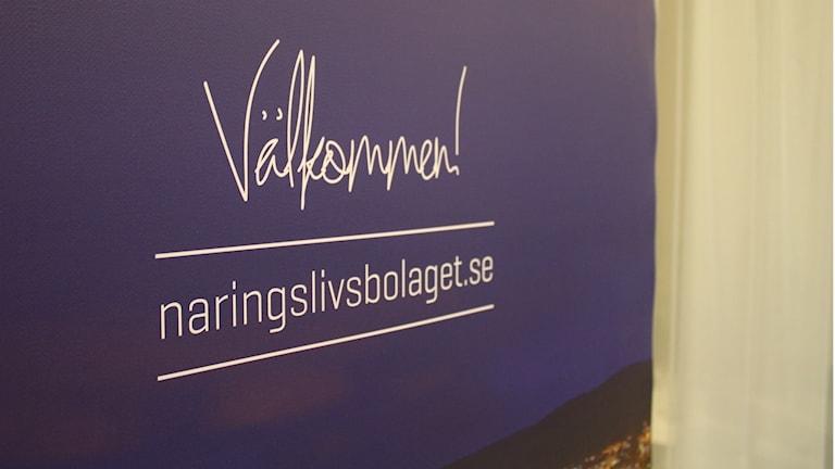 En lila skylt med texten Välkommen! Under välkommen står det naringslivsbolaget.se