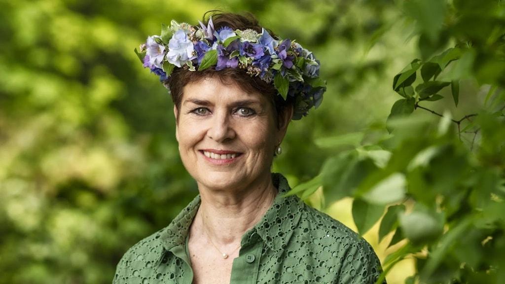 Sommarvärden Ullakarin Nyberg fotograferad i lummig miljö. På huvudet har hon en blomsterkrans. Hon har på sig en mörkgrön sjal och hon ler mot kameran.