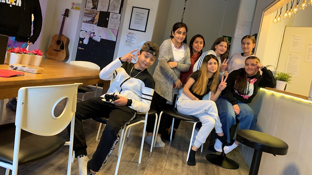 En grupp unga som sitter i fritidsgårdslokal