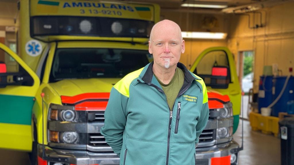Ambulansföraren Magnus Häggqvist är iförd arbetskläder och står framför en ambulans som är parkerad i ett garage. Han har händerna knäppta bakom ryggen och tittar in i kameran.