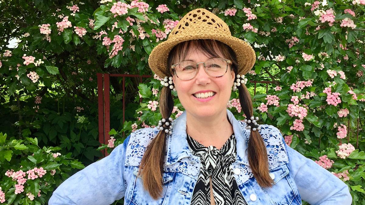 Agneta Olsson i hatt framför grön blommande häck. Foto: Karin Lönnå/Sveriges Radio