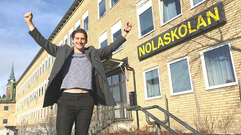 Dennis Westergård sträcker armarna i skyn framför Nolaskolan