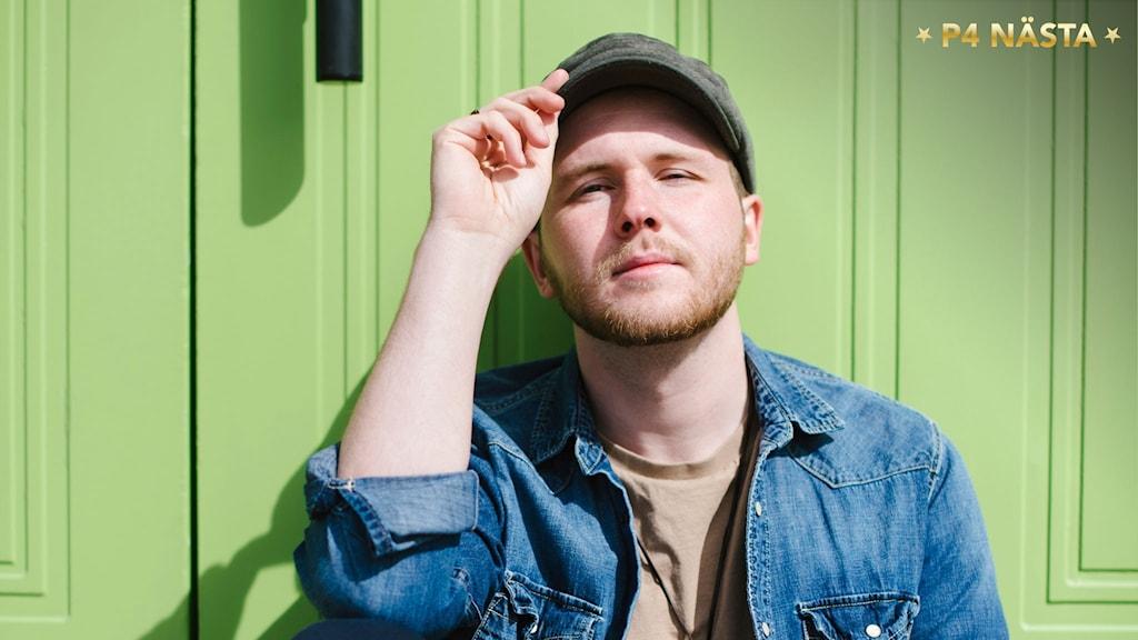 Porträtt August Erikn när han sitter mot en pistagegrön vägg och solar sig med handen på skärmkanten av kepsen. Foto: Petra Berggren/Sveriges Radio