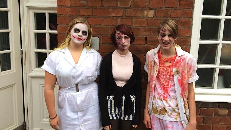 Tre ungdomar i Halloweenutklädnad