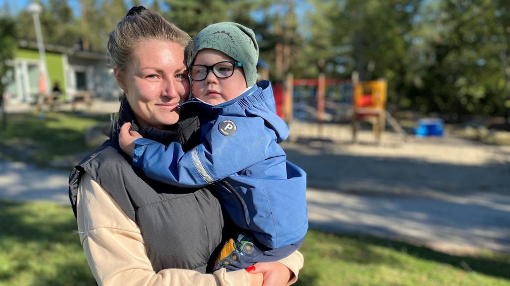 Mamma håller sin 2-årige son i famnen ute på förskolan.