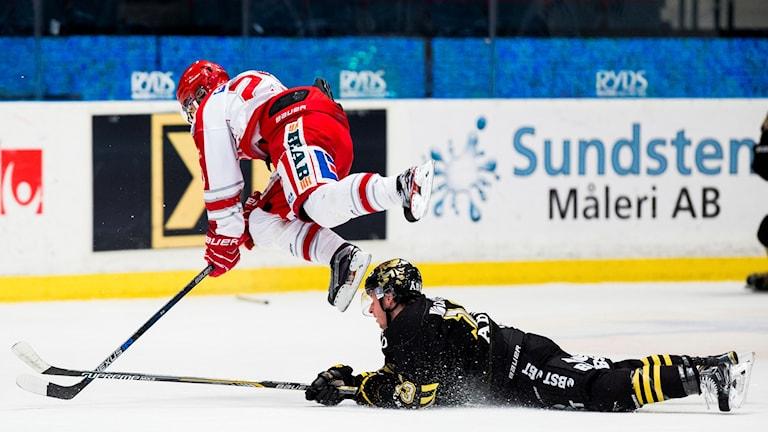 Timrås Jeremy Boyce-Rotevall bjuds på en flygtur av AIK:s Marcus Jonsson under ishockeymatchen i Hockeyallsvenskan mellan AIK och Timrå den 5 januari 2016 i Stockholm.