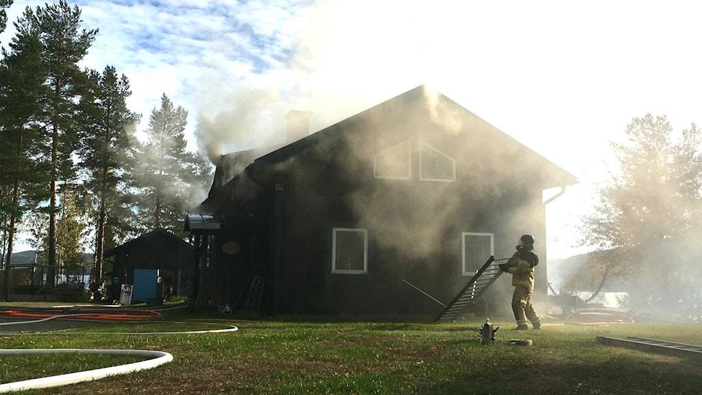 En brandman hanterar en stege framför ett brinnande hus.